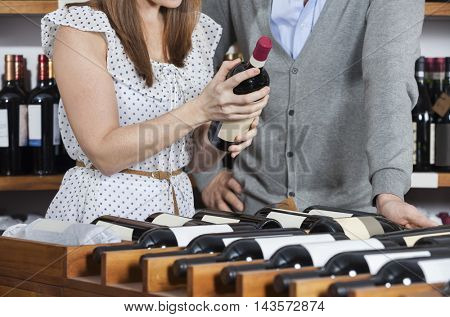 Midsection Of Woman Holding Wine Bottle While Man