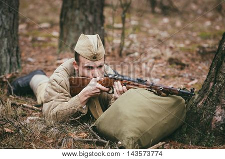 Pribor, Belarus - April, 04, 2015: Unidentified re-enactor dressed as Soviet russian soldier aiming a rifle at enemy