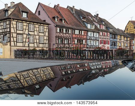 COLMAR FRANCE - 30TH JULY 2016: A view of colourful timber framed buildings along Little Venice in Colmar. Reflections can be seen.