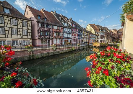 COLMAR FRANCE - 30TH JULY 2016: A view of colourful timber framed buildings along Little Venice in Colmar during the morning. Reflections can be seen in the River Lauch