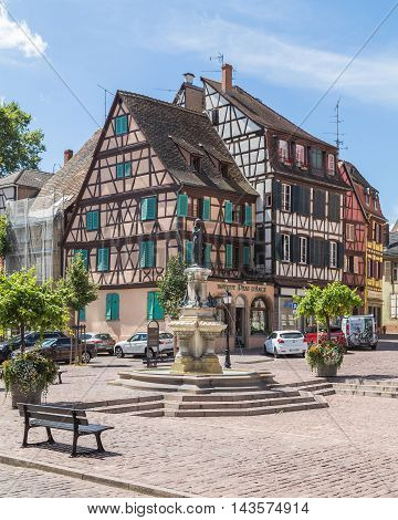 COLMAR FRANCE - 30TH JULY 2016: A view of colourful timber framed buildings in Colmar during the day. The Roesselmann fountain can be seen.