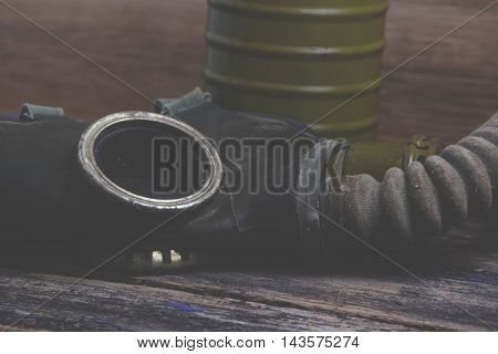 Old and dirty gas mask on wood background