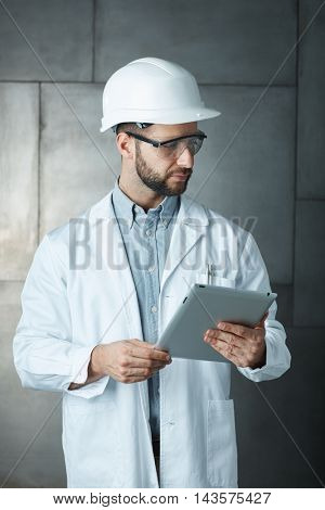 Portrait of confident young engineer wearing protective hardhat using tablet.