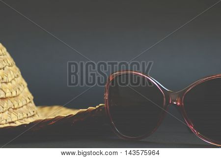 Vintage straw hat and retro sunglasses on background