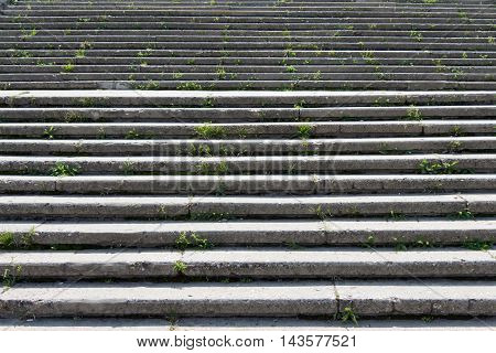 Stone (concrete) stairs with lots of steps. The light falls at an angle and creates a shadow. In the crevices the grass grow. The background is blurred.