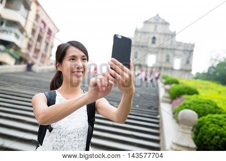 Woman taking selfie by mobile phone in Macao