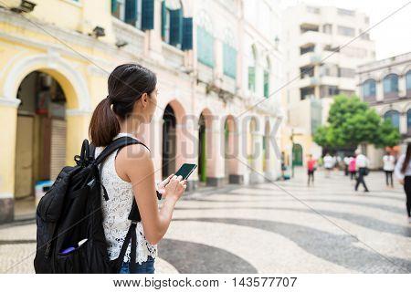 Woman backpacker using cellphone