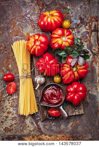 Ripe tomatoes, tomato sauce and seasonings, top view. Italian cuisine. Ingredients for cooking pasta.
