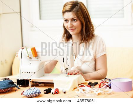 Young woman is sewing at home. Hobby Time.
