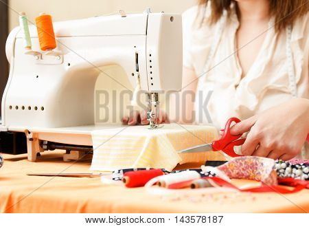 Young woman is sewing at home. Close up.