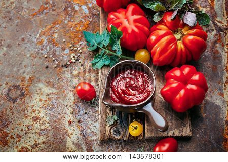 Tomato sauce and fresh tomatoes on the table with copy space . May be used as background