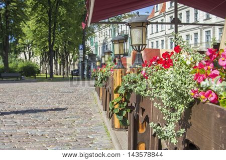 background view of the street in the old town of Riga and deserted street cafe with lanterns and flowers