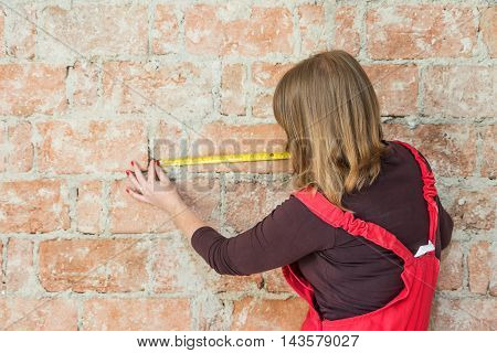 Rear view of a young woman measuring a brick wall. Horizontally.