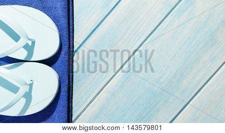 beach accessories. stylish sunglasses with towel and flip flops on blue wooden table