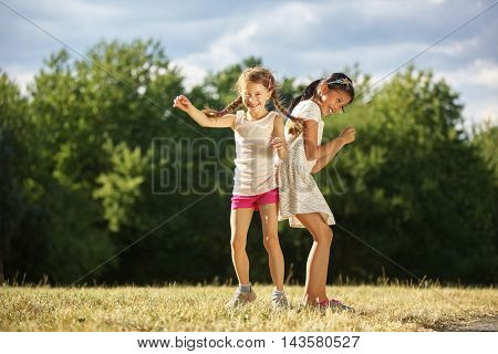 Two grils under the sunshine dancing in summer at the park