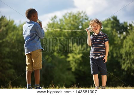Two boys play with tin can telephone playing in the nature