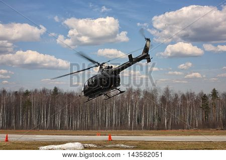 The aircraft - the black helicopter at competitions makes flight at low height on cloudy sky background.