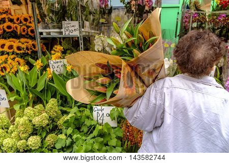 Rear view of unrecognizable female customer holding two bunches of fresh flowers at street flower shop.LondonEngland.