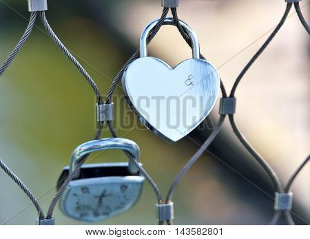 Heart shaped padlock with copy space on a fence. Romantic love symbol.