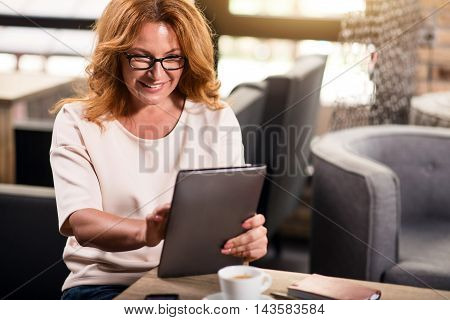 Stay modern. Cropped image of smiling businesswoman sitting at the table with cup of coffee and holding digital tablet