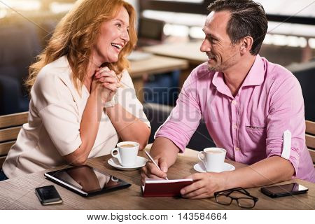Discussion. Cheerful and content business partners discussing some things while being in cafe