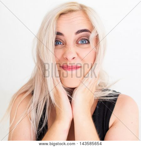 Young woman play the ape on white background. Close-up photo of funny blonde grimacing her face. Playful, joyful mood of female adult
