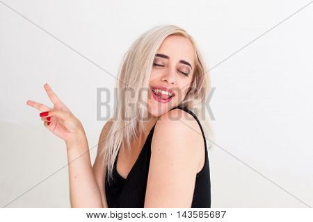 Portrait of cheerful woman with peace hand sign. Drunk playful blonde in black dress with closed eyes laughing and posing jocosely at camera, white background