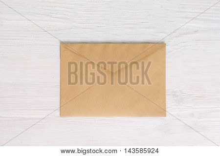 Empty envelope blank on white wooden background, flat lay. Brown paper container, vintage document package, post delivery concept