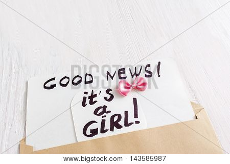 Card it's a girl with pink bow, close-up. Note with congratulation about newborn child gender, white wooden background, free space