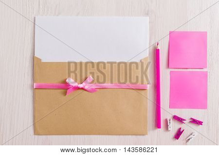 Set for making handmade greeting card, flat lay. Top view on kit of envelope with blank paper and pink ribbon, pencil, pins and sticker on white background. It's a girl note concept