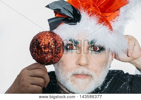Bearded man with serious face and makeup on his eyes in santa claus hat holding red sparkling chrismas ball near head on white background studio