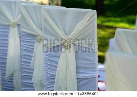 White chairs wedding arrangement decorated with beautiful creamy knot of ribbon and sparkling shiny brooch on natural background outdoor