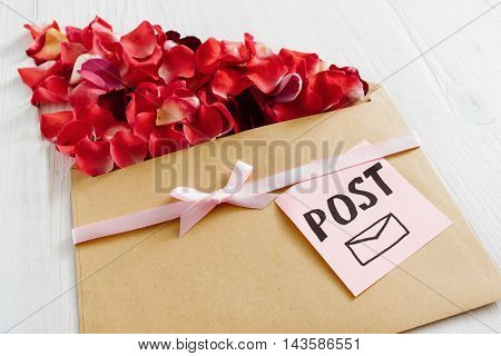 Romantic post message with flower petals, closeup. Floral composition of rose bloom and kraft paper on white wooden background, romantic present
