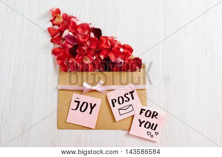 Joy for you post with red rose petals, flat lay. Joyful romantic composition with flower bloom and paper envelope, white wooden background, copy space