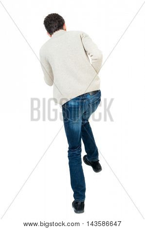 back view of guy funny fights waving his arms and legs. Isolated over white background. Rear view people collection.  backside view of person. Curly short-haired man in a woolen white jacket jumping