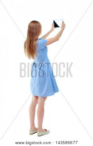 back view of standing young beautiful  woman  using a mobile phone. girl  watching. Rear view people collection.  backside view of person.  Isolated over white background. Skinny girl in blue dress