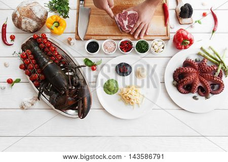 Chef preparing marbled beef, flat lay, copy space. Top view on cook workplace ingredients for cooking, white wooden background. Italian cuisine, culinary classes, restaurant kitchen concept