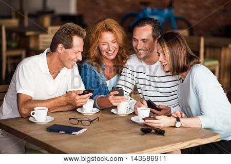 Usual day. Delighted and smiling men and women using their mobile phones while sitting at the table and drinking good coffee