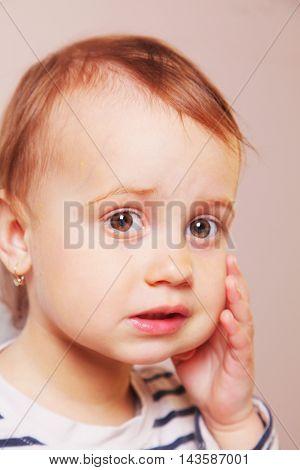 cute little baby girl having toothache (closeup)