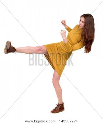 skinny woman funny fights waving his arms and legs. Isolated over white background. Long-haired brunette in a mustard-colored falls.