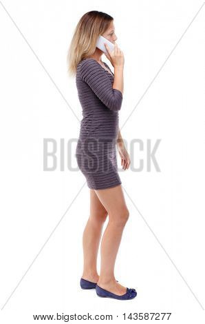 back view of a woman talking on the phone.  backside view of person.  Rear view people collection. Isolated over white background. Blonde in violet short dress talking on the phone while walking.