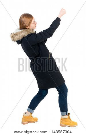 Side view. girl in winter jacket pulls his hands on top of the rope   Standing young girl in parka. Rear view people collection.  backside view of person.  Isolated over white background. The girl in