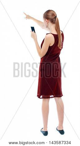 back view of pointing young beautiful  girl with tablet computer. girl  watching. Rear view people collection.  backside view of person.  Isolated over white background.  A girl in a burgundy dress