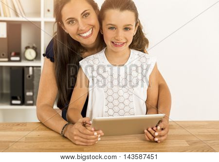 Mother and daughter at home using a tablet