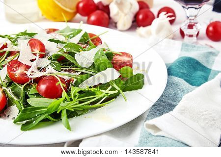 Fresh, summer salad with halves of cherry tomatoes, fresh arugula leaves, grated parmesan and lemon zest on white plate. Near are garlic, tomatoes, lemon, glass of wine and blue napkin with forks on