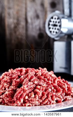 Pinky raw ground beef on a white plate with meat grinder near it. Ground beef can be used to cook hamburgers, chili con carne or other dishes. Wood background.