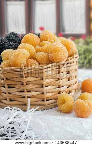Fresh yellow raspberries in a small wicker basket.