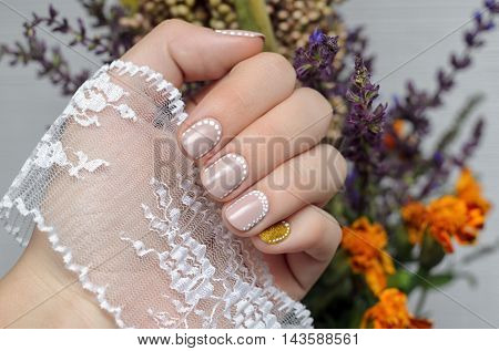 Female hand with warm beige nail design holding lace