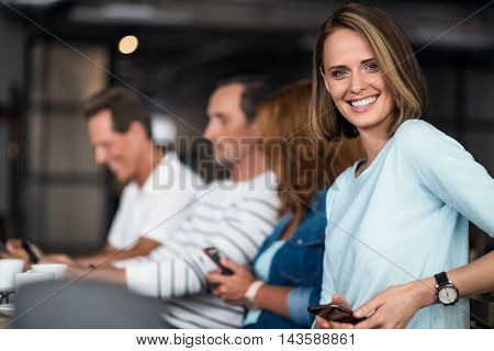 One wave. Smiling and delighted young woman holding smart phone and laughing at a camera with another people using phones in background