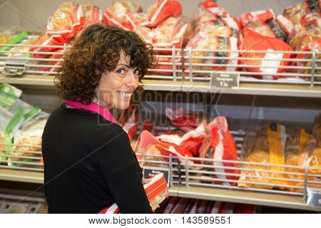 Cheerful European Woman Picking Bread From Shelf In Food Store